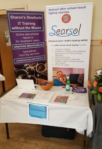 Table at exhibition with Sharon's Shortcuts banner and Searsol banner